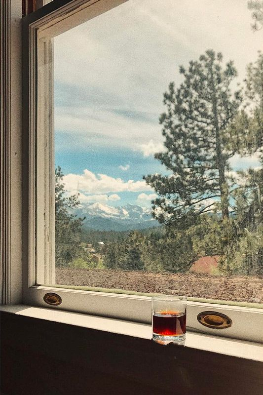 cocktail set in the window with snowey mountains in the background