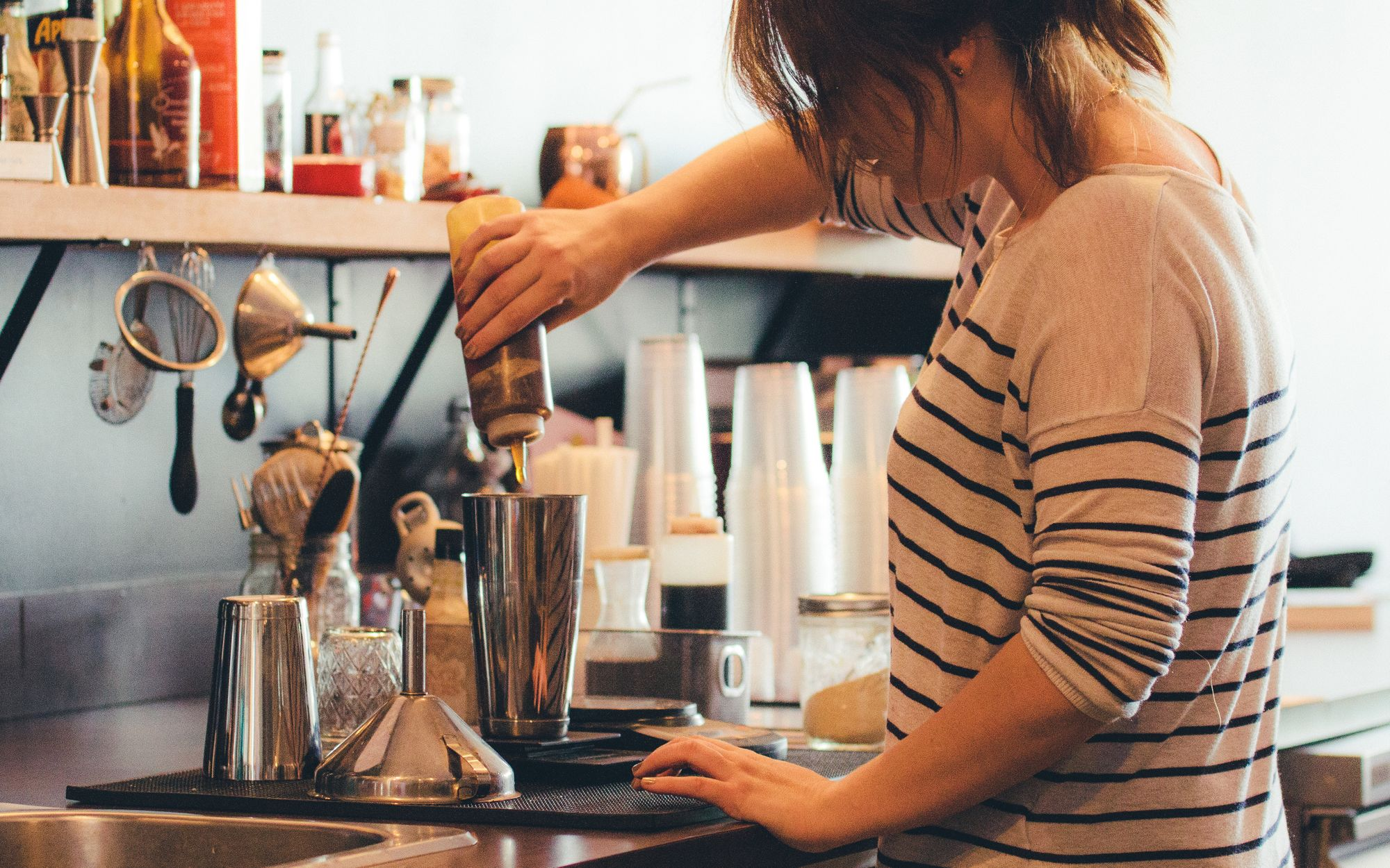 barista pouring syrup from squeeze bottle