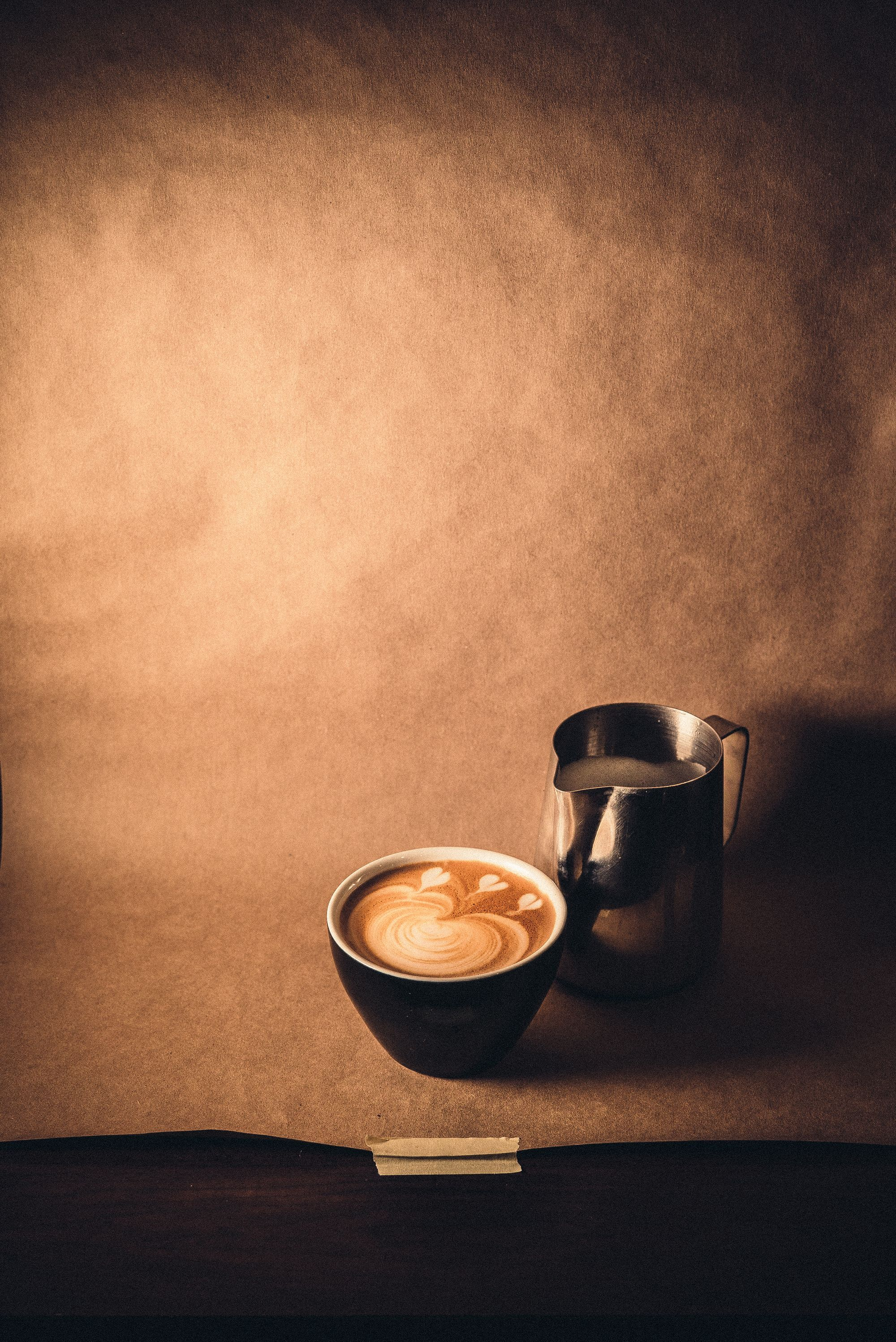 Photo of a latte and a milk pitcher.