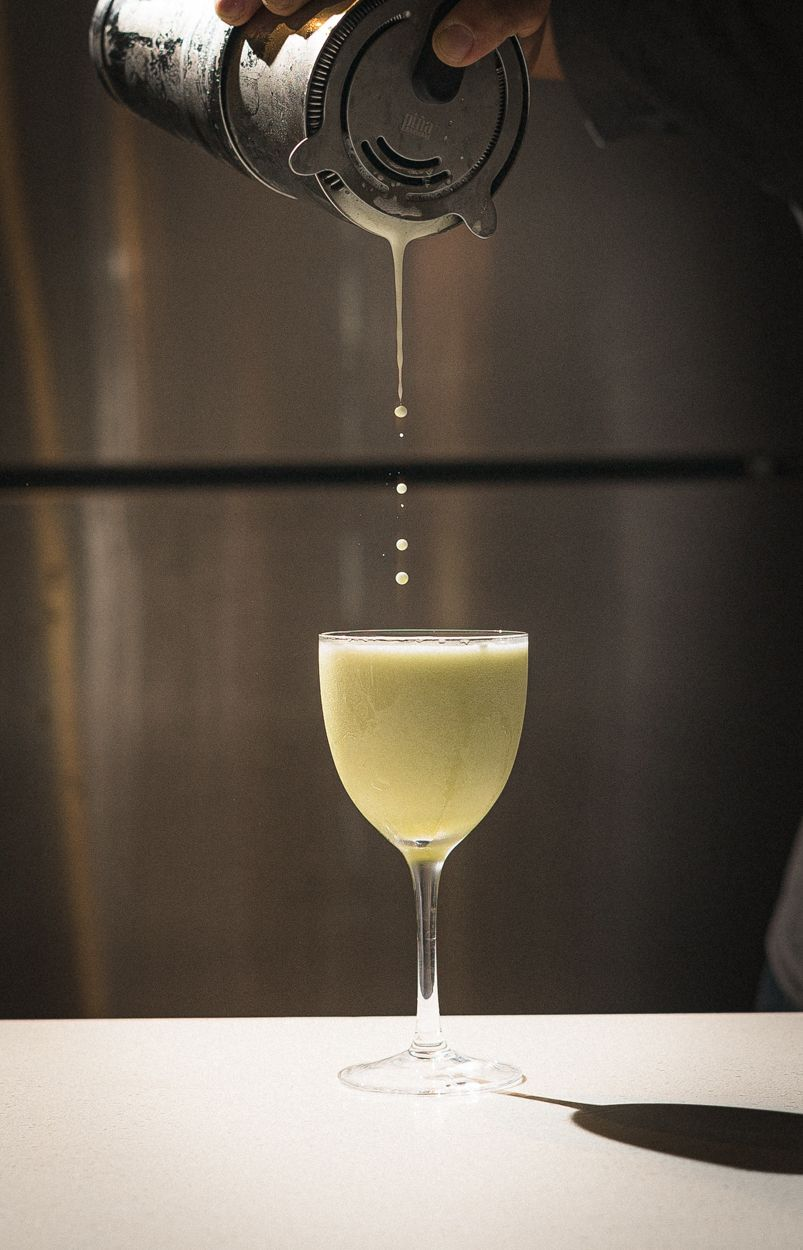 straining drops into cocktail glass