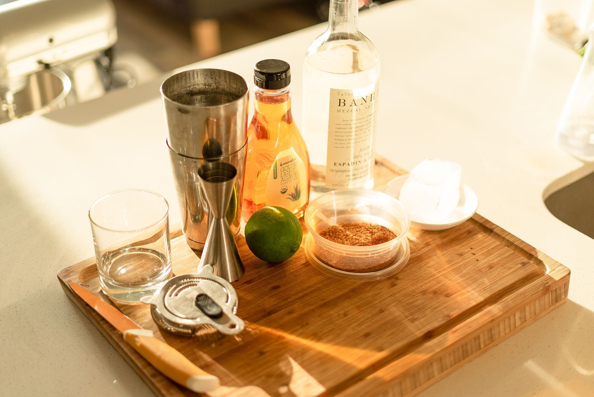 ingredients for making a mezcal margarita over a thick cutting board