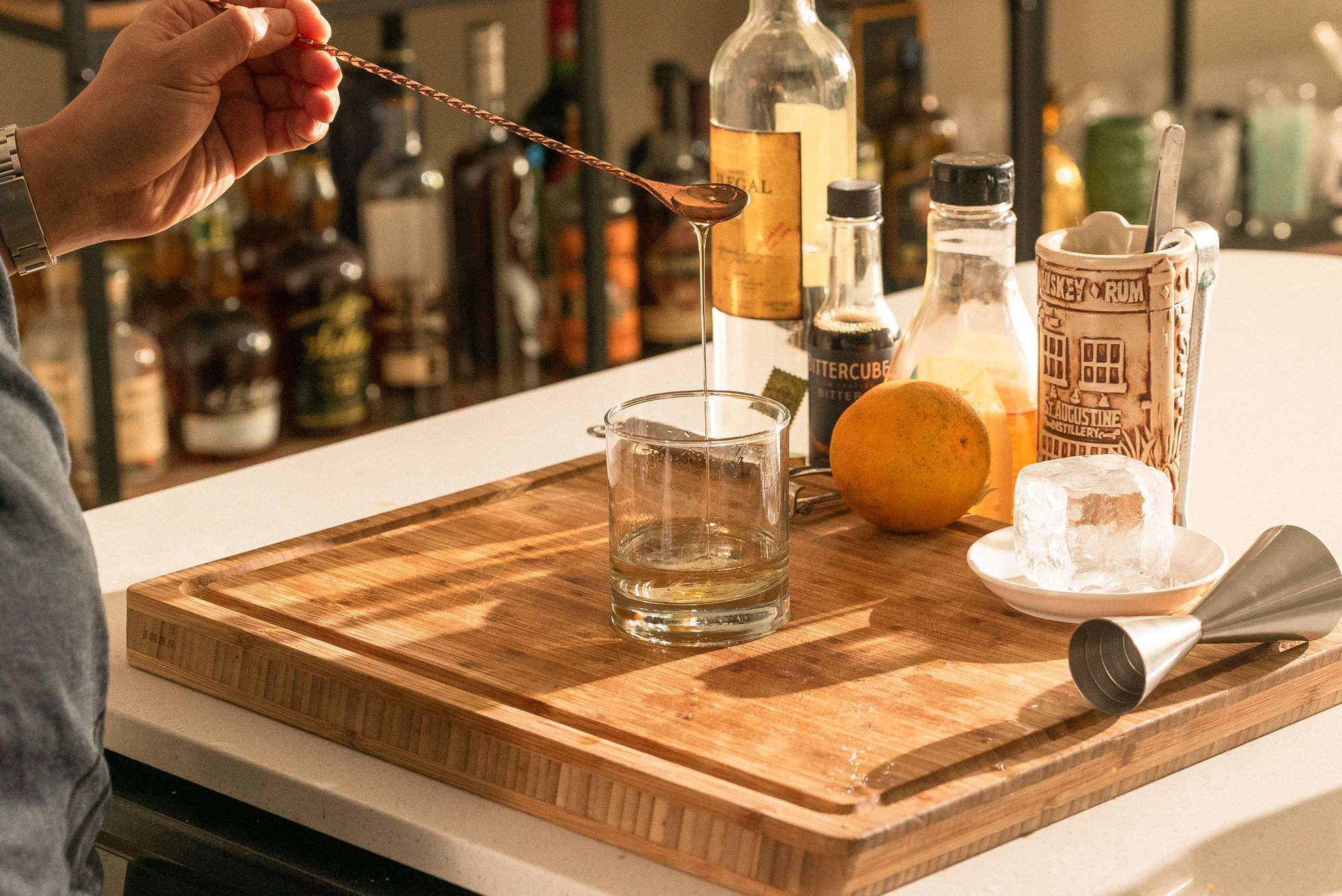 adding a barspoon of agave syrup to the rocks glass