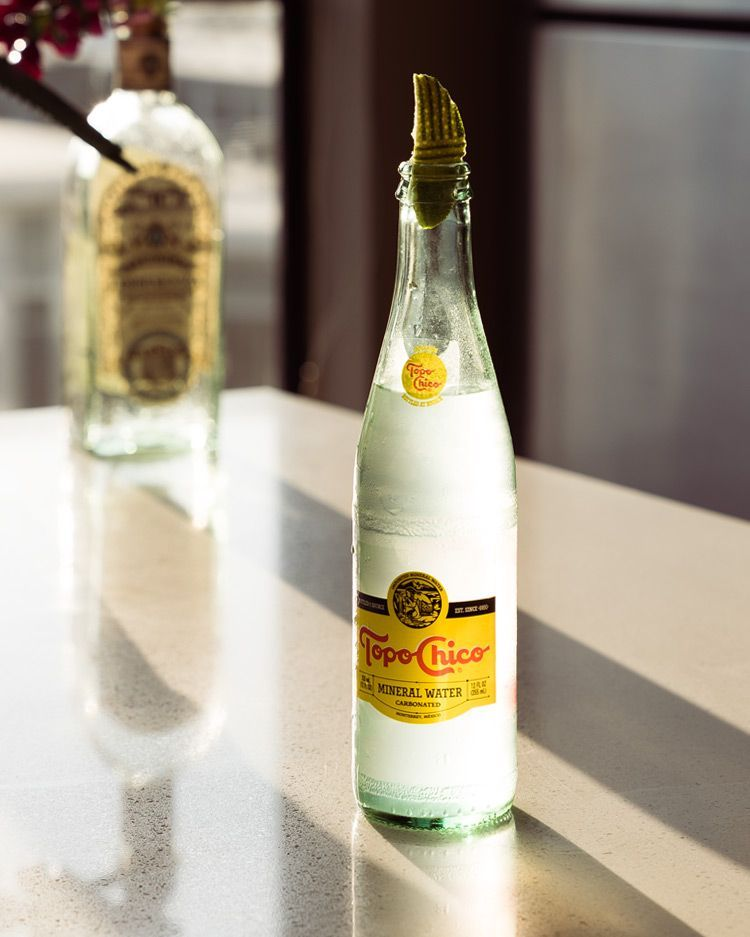 cold bottle of topo chico with a lime on top