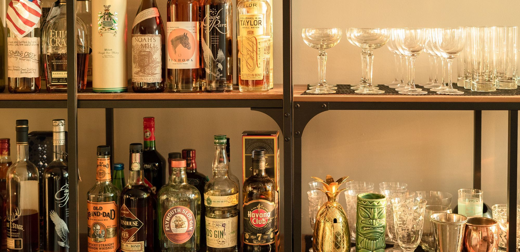home bar setup with many bottles, assorted glassware in an afternoon warm glow.