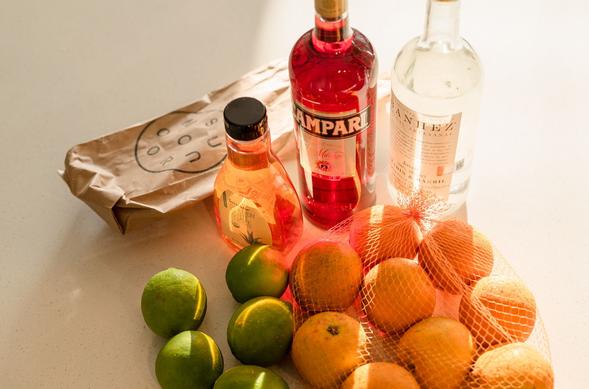 picture of agave syrup, campari, mezcal, limes and oranges.
